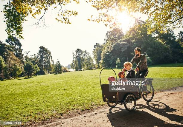 cycling through the park - family stock pictures, royalty-free photos & images
