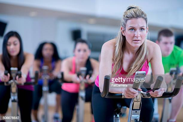 cycling together in exercise class - spinning stock pictures, royalty-free photos & images