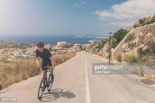 cycling up the cumbre del sol - カルペ ストックフォトと画像