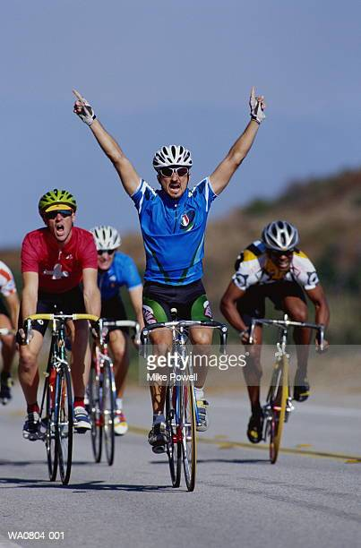 Cycling, winner crossing finishing line with arms raised