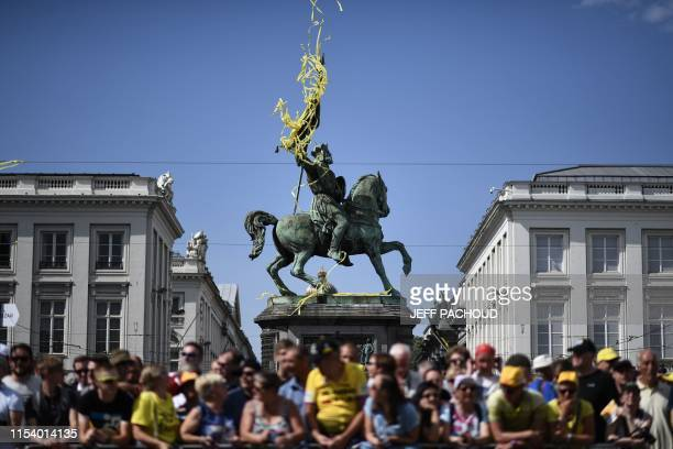 Cyclism enthusiasts wait under the statue of Godefroy de Bouillon at the Place Royale - Koningsplein Square before the first stage of the 106th...