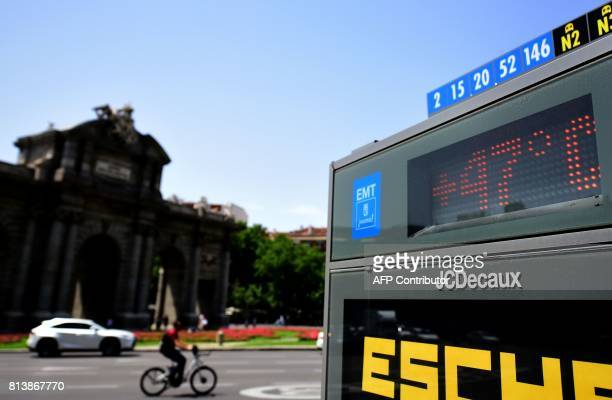 A cyclist and a car pass by a city digital board indicating 47 degrees Celsius at Puerta de Alcala in Madrid during a heat wave on July 13 2017 / AFP...