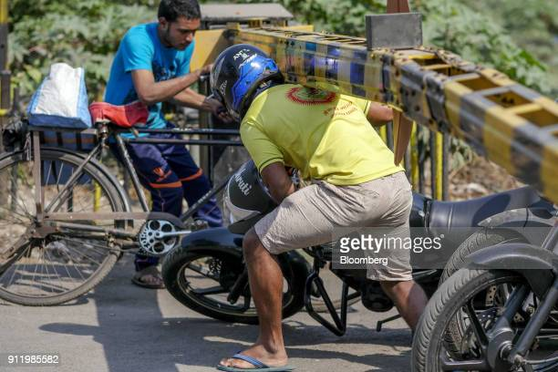 A cyclist and motorcyclist duck underneath the barrier of a railway crossing near Sewri railway station in Mumbai India on Saturday Jan 27 2018...