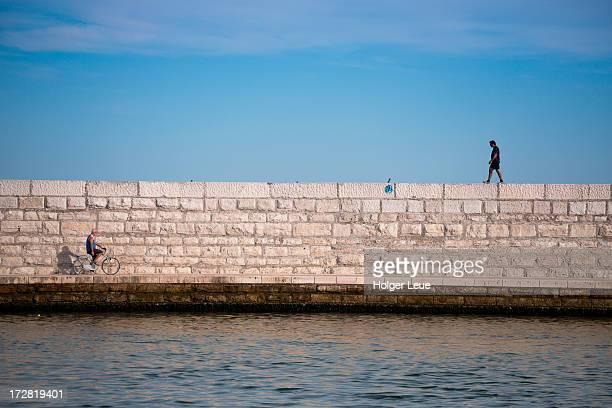 Cyclist and pedestrian on Venice lagoon seawall