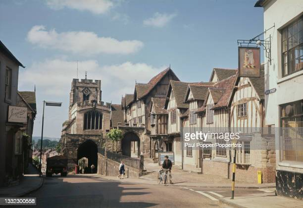 Cyclist and pedestrian walk up the High Street past Lord Leycester Hospital with Westgate, one of the original three gates in the town of Warwick, in...
