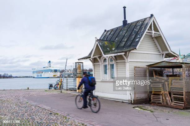 Cyclist and wooden kiosk in Helsinki port.