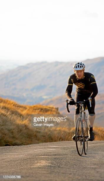 cyclist approaching top of hill in the british lake district - wielrennen stockfoto's en -beelden