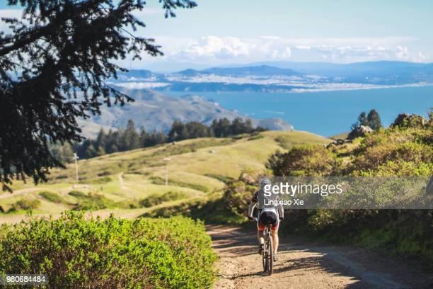 cyclist biking on bolinas ridge with ocean view, mt tamalpais, california - mountain ridge stock pictures, royalty-free photos & images