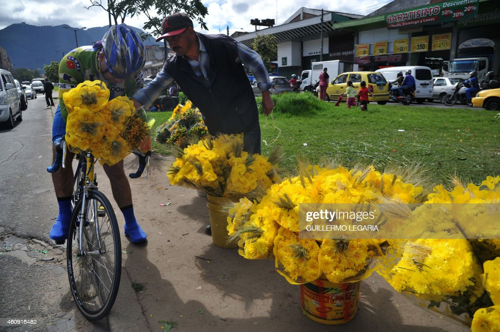 A cyclist buys a bouquet of yellow flowers, used for New Year's rituals, at a street of Bogota, Colombia, on December 30, 2014. In great part of Latin America, New Year is celebrated with deeply rooted omens as wheat ears and yellow flowers, herb and champagne baths, walking around the block with a suitcase, having lentils in the pocket, putting potatoes under the bed and the ritual of the 12 grapes. AFP PHOTO/Guillermo LEGARIA /