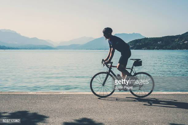 cyclist by lake annecy, france - フランス アヌシー ストックフォトと画像