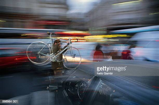 cyclist carrying bike over bonnet of car (blurred motion) - nello stock pictures, royalty-free photos & images