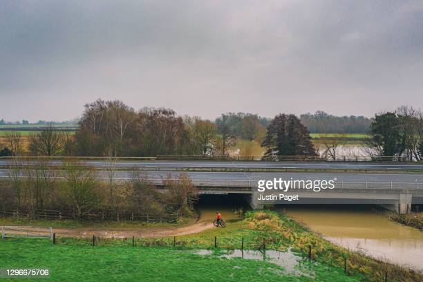 cyclist checking route on flooded dirt track - motorway stock pictures, royalty-free photos & images