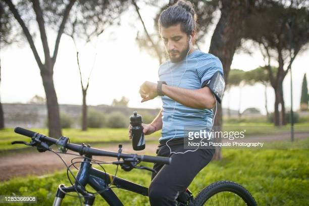 cyclist checking smart watch - watch what happens: live stock pictures, royalty-free photos & images