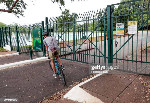 A cyclist circles back at the closed gates of Ibirapuera Park during a lockdown aimed at stopping the spread of the coronavirus pandemic on March 21...