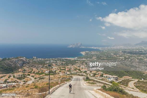 cyclist climbing cumbre del sol - calpe stock pictures, royalty-free photos & images