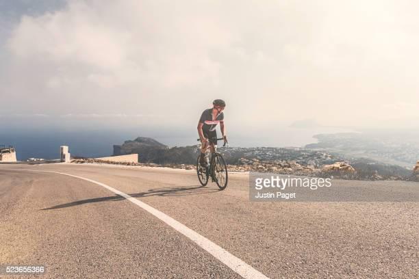 Cyclist climbing up Cumbre Del Sol, Benitachell, Spain