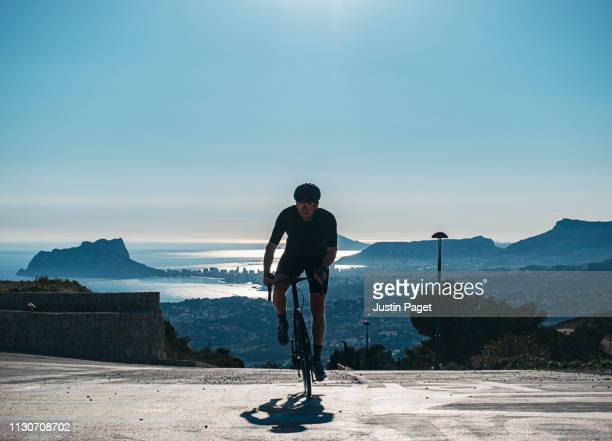 cyclist climbing with view of calpe behind - calpe stock pictures, royalty-free photos & images