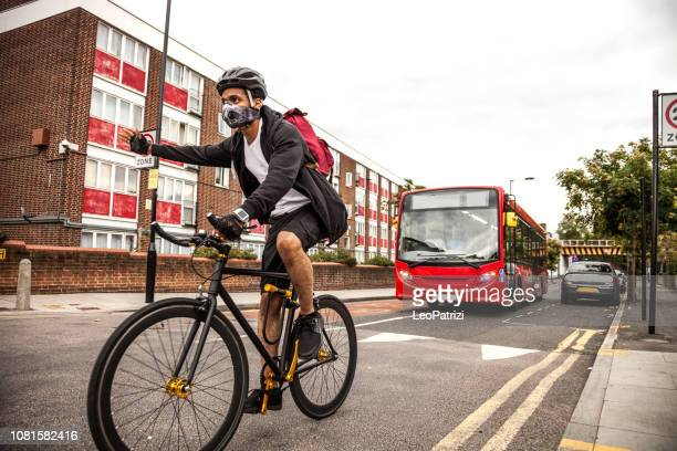 cyclist commuter wearing a pollution-mask in central london - air pollution stock pictures, royalty-free photos & images