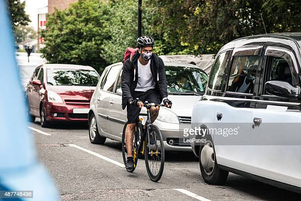 cyclist commuter wearing a pollution-mask in central london - cycling stock pictures, royalty-free photos & images