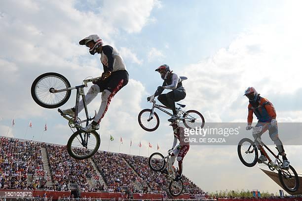 Cyclist Connor Fields, Britain's Liam Phillips, Latvia's Edzus Treimanis and Netherlands' Raymon van der Biezen take a jump during the BMX cycling...