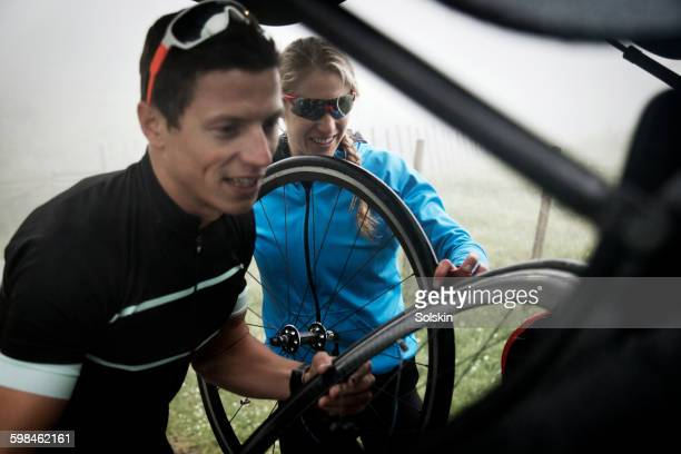 cyclist couple packing gear into car - unloading stock pictures, royalty-free photos & images