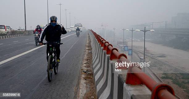 A cyclist covered his nose with a handkerchief to save himself from the polluted air near India gate on December 12 2015 in New Delhi India