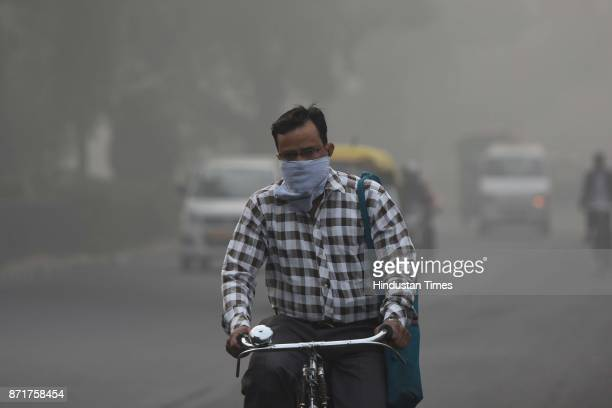 A cyclist covers his face amid heavy smog on November 8 2017 in New Delhi India Delhi was enveloped in a thick blanket of haze for the second...