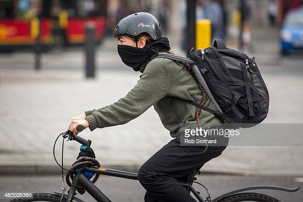 A cyclist covers their face whilst riding through Charing Cross on April 2 2014 in London England Dust from the Sahara combined with pollution from...