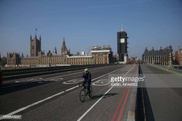 A cyclist crosses a nearempty Westminster Bridge with the Houses of Parliament in the background in central London on April 9 2020 British Prime...