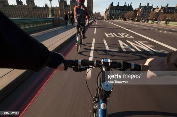 A cyclist crosses Westminster Bridge towards the Houses of Parliament, London, England, United Kingdom, Europe