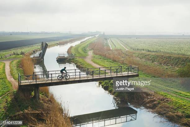 cyclist crossing bridge over river - river stock pictures, royalty-free photos & images