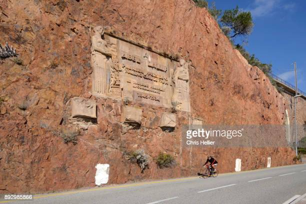 Cyclist Cycles Past Memorial to Touring Club of France Tourism Association, Esterel Corniche, Théoule-sur-Mer, French Riviera.