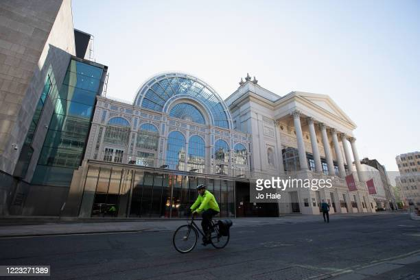 Cyclist cycles past the closed Royal Opera House in Covent Garden on May 06, 2020 in London. The country continued quarantine measures intended to...