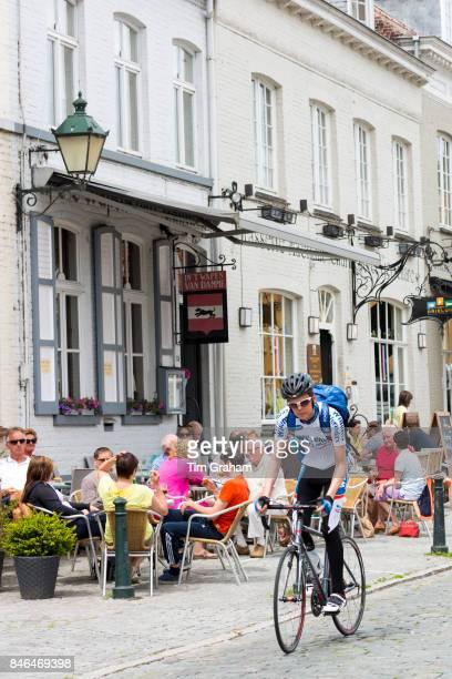 Cyclist cycling past al fresco diners at restaurant in Kerk Straat Damme West Flanders Belgium