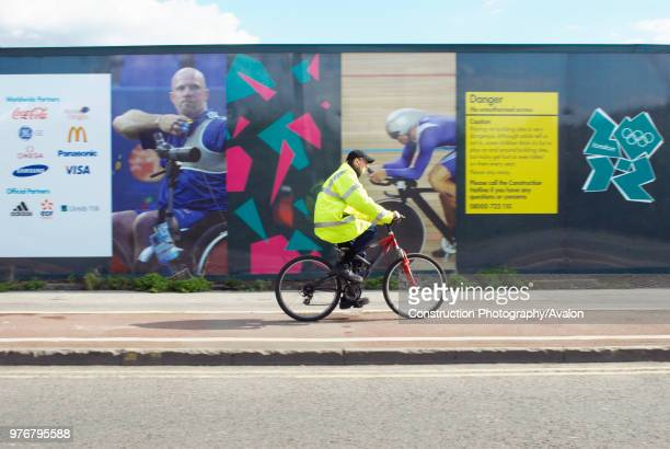 Cyclist cycling past Olympic construction site hoardings, Stratford, London, UK, 2008.