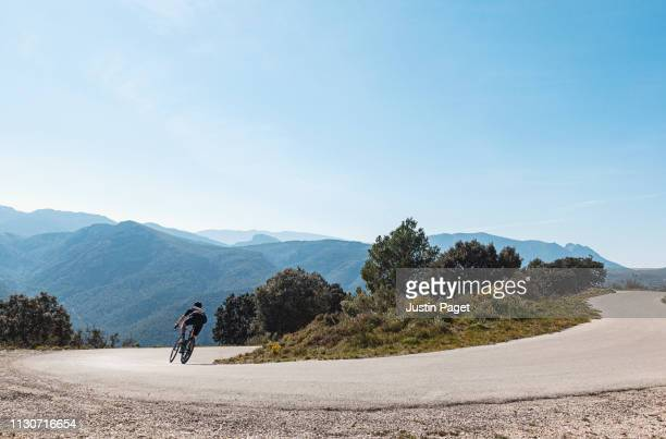 cyclist descending around hairpin near benigembla - wielrennen stockfoto's en -beelden