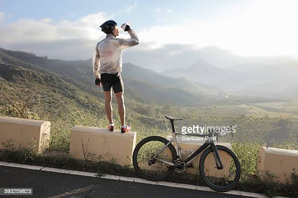 Cyclist drinking and looking at view