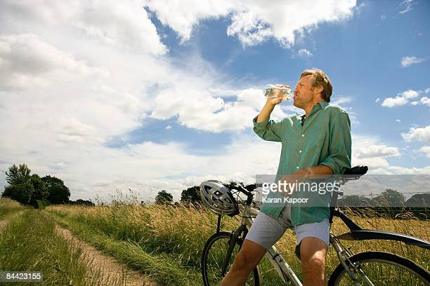 cyclist drinking from a bottle of water - アマシャム ストックフォトと画像