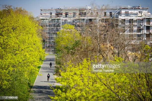 A cyclist drives on a bike path on a construction site with newly built residential buildings on April 16 2019 in Berlin Germany
