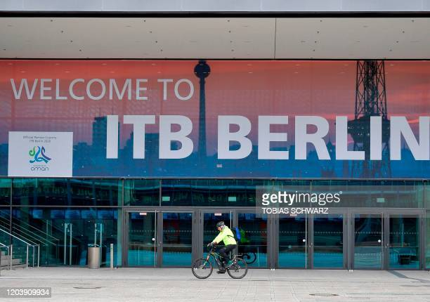 A cyclist drives past a banner promoting the International Travel Fair at the fair grounds in Berlin on February 28 2020 Authorities will decide on...