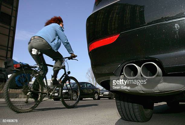 A cyclist drives past a parked car and its exhaust pipe on March 29 2005 in Berlin Germany Many German cities are close to violating EUregulated...