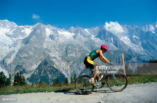 Cyclist during a mountain bike competition with the Mont Blanc massif in the background Courmayeur Aosta Valley Italy