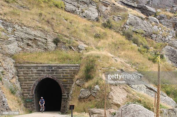 cyclist exits a tunnel on the otago rail trail - otago region stock pictures, royalty-free photos & images