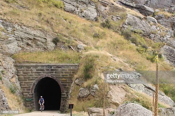 cycliste sorties un tunnel sur le sentier de la gare ferroviaire de d'otago - otago photos et images de collection