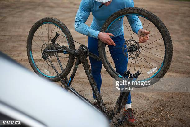 Cyclist fitting bicycle wheel to upside down bicycle