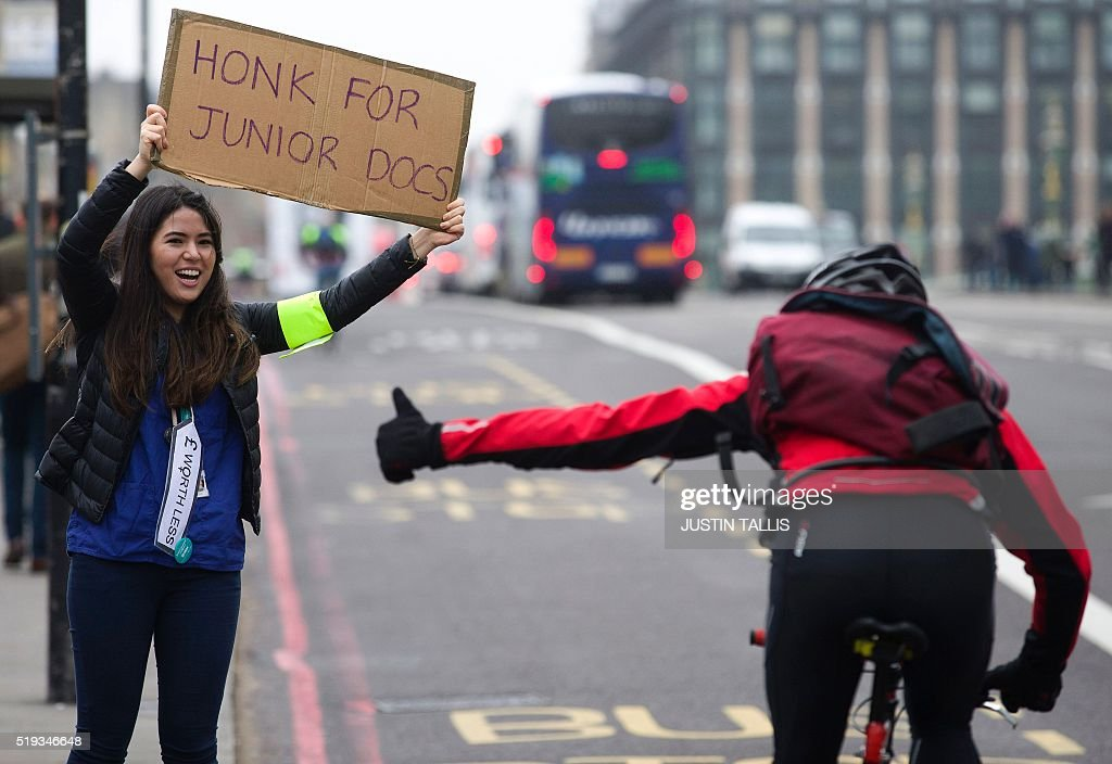 A cyclist gestures as they pass a demonstrator holding a placard during a Junior Doctors' strike outside St Thomas' Hospital in central London on April 6, 2016, against proposed new conditions and pay rates for working unsociable hours. Thousands of operations and procedures across England have been cancelled as a result of the 48 hour strike which began Wednesday morning. / AFP / JUSTIN