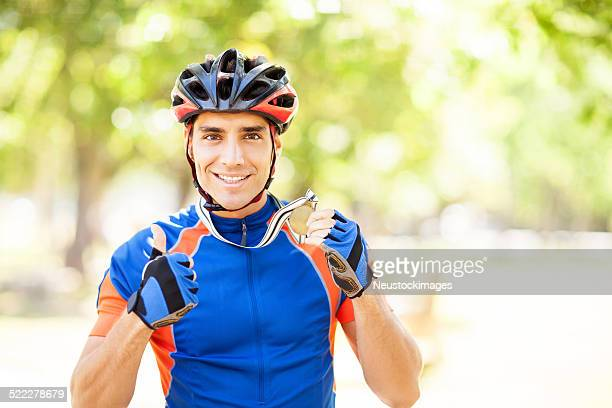 Cyclist Gesturing Thumbs Up While Holding Gold Medal