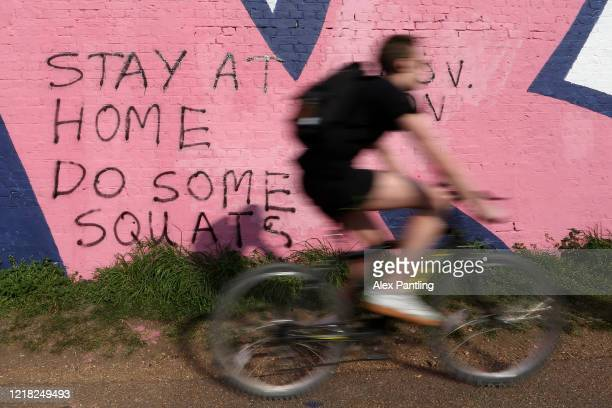 Cyclist goes past graffiti asking people to stay at home at Queen Elizabeth Olympic Park on April 11, 2020 in London, England. Public Easter events...