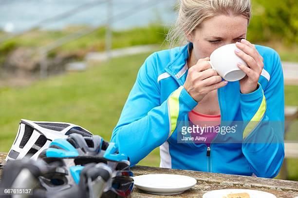 Cyclist having breakfast at picnic table