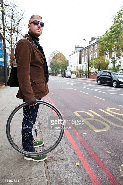 cyclist holding bike wheel - kerb stock pictures, royalty-free photos & images